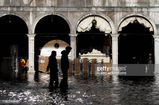 People walk across the flooded St Mark's Square on November 14 2019 in Venice Much of Venice was left under water after the highest tide in 50 years...