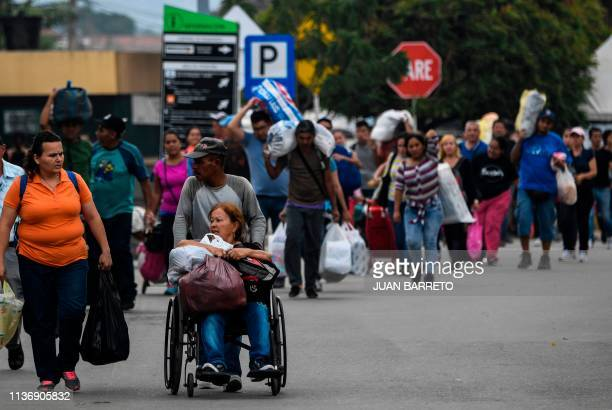 People walk across the international border bridge Simon Bolivar between the Colombian city of Cucuta and San Antonio del Tachira in Venezuela on...