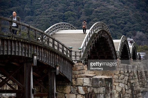 People walk across the Kintaikyo wooden arch bridge in Iwakuni Yamaguchi Prefecture Japan on Monday Jan 6 2014 Gross domestic product expanded an...