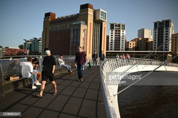 People walk across the Millennium Bridge on the River Tyne in the early evening sunshine in Newcastle upon Tyne, north-east England, on September 17,...
