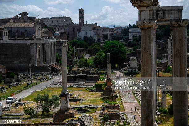 People walk across the Roman Forum, as seen from the Capitoline Museum in Rome as it reopens on May 19, 2020 while the country's lockdown is easing...