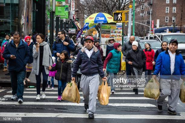 People walk along 37th Avenue Saturday December 15 in Jackson Heights New York It is considered one of the most diverse communities in the United...