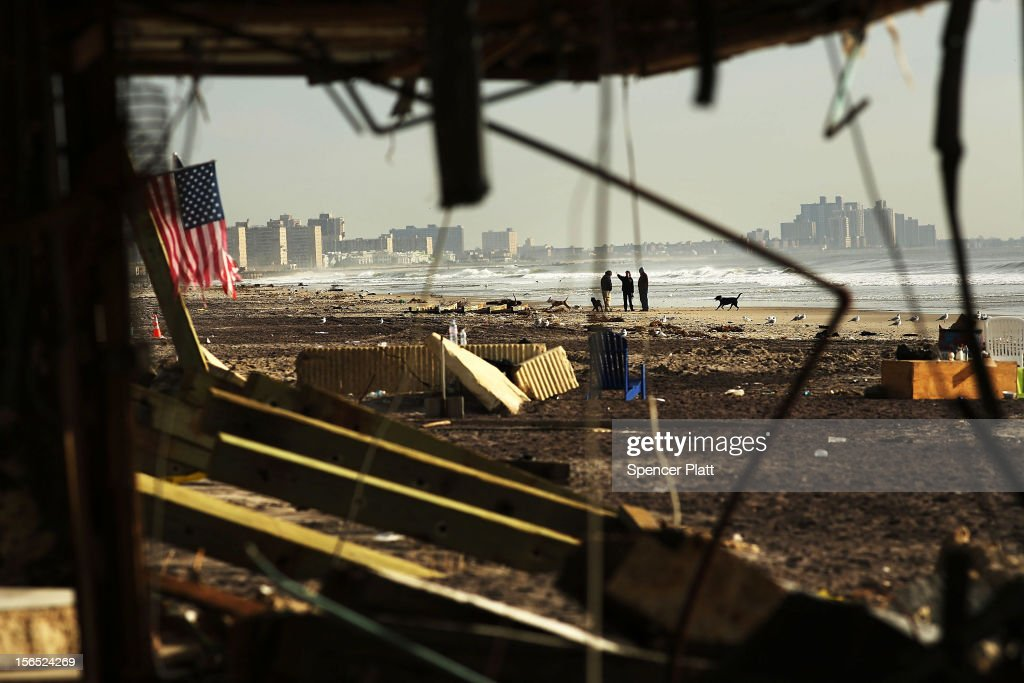 People walk along a beach amidst debris in the heavily damaged Rockaway neighborhood where a large section of the iconic boardwalk was washed away on November 16, 2012 in the Queens borough of New York City. More than two weeks after Superstorm Sandy slammed into parts of New York and New Jersey, thousands are still without power and heat.