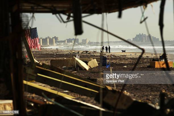 People walk along a beach amidst debris in the heavily damaged Rockaway neighborhood where a large section of the iconic boardwalk was washed away on...