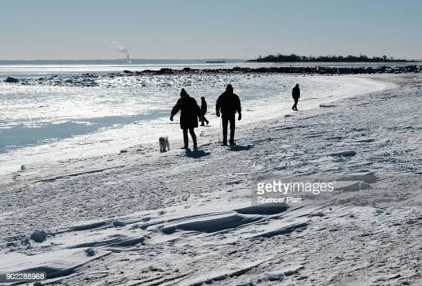 People walk along a beach covered in snow and ice as temperatures continue to stay below freezing in much of the Northeast on January 7 2018 in...