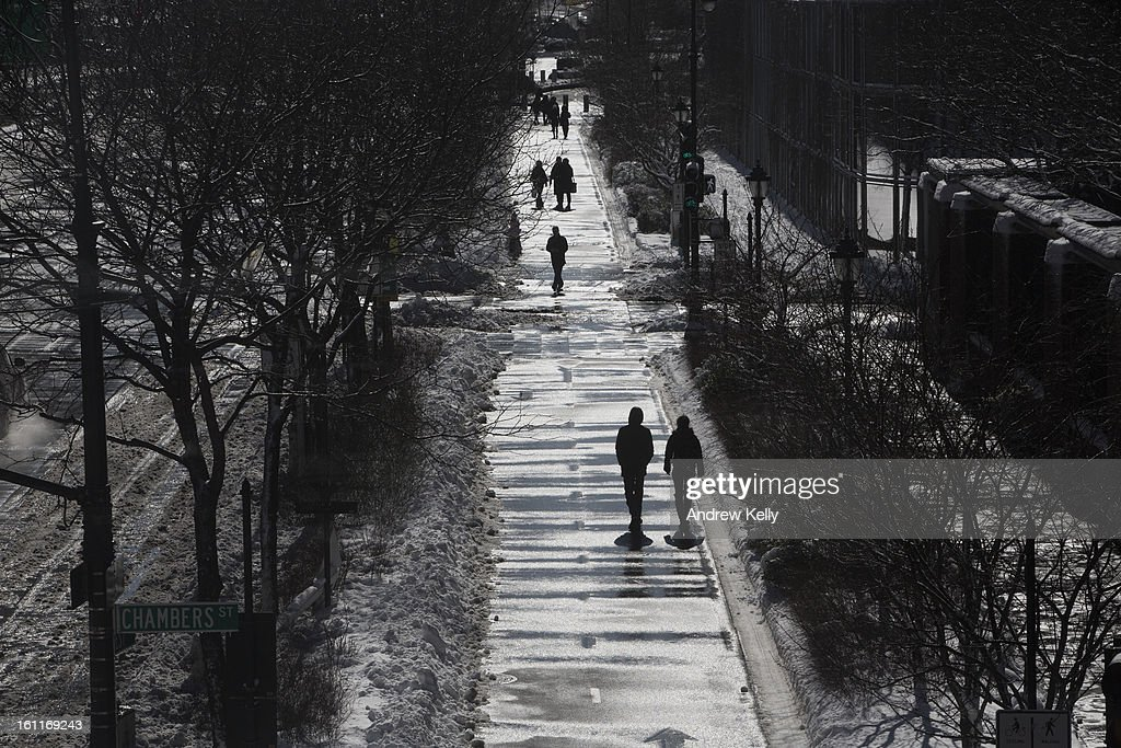 People walk along a cleared bike path following a major winter storm on February 9, 2013 in New York City. New York City and much of the Northeast received a foot or more of snow overnight. Heavy snow warnings are in effect from New Jersey through southern Maine.