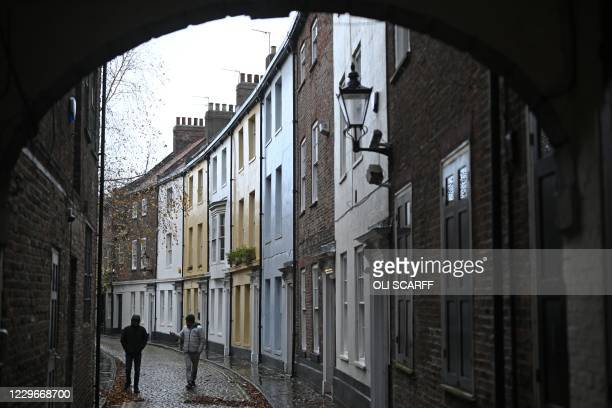 People walk along a cobbled street in the rain in Hull, in north-east England on November 18 following a rise in the number of novel coronavirus...