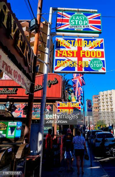 People walk along a commercial street full of British businesses in Benidorm on January 31 2020 On the sundrenched eastern coast of Spain British...