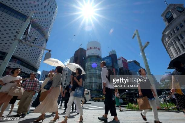 TOPSHOT People walk along a crossing on a sunny day in Tokyo's Ginza shopping district on June 29 2018 The Japan Meteorological Agency announced on...