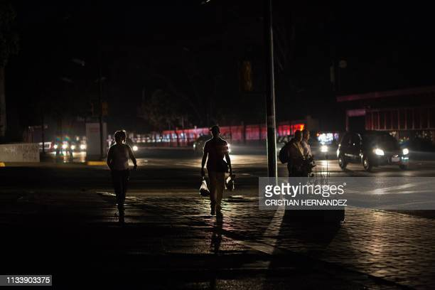 People walk along a dark street during a new power outage in Caracas on March 30 2019 Venezuelan security forces fired tear gas Saturday to disperse...