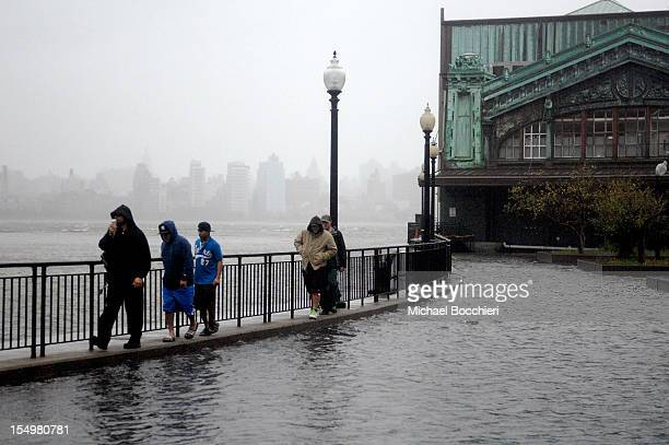People walk along a fence of the flooded ErieLackawanna Park as Hurricane Sandy moves into the area on October 29 2012 in Hoboken New Jersey The...