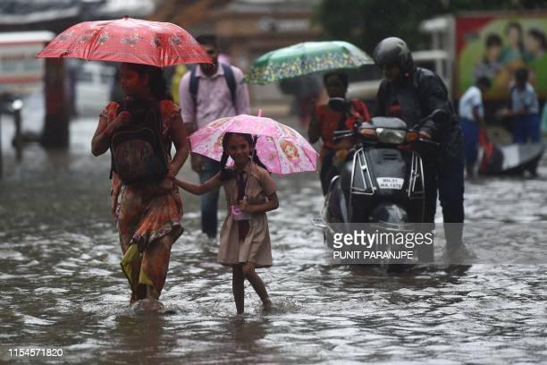 People walk along a flooded road after heavy monsoon rain in Mumbai on July 8 2019