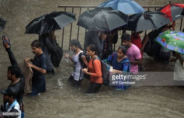 People walk along a flooded street during heavy rain showers in Mumbai on August 29 2017 Heavy rain brought India's financial capital Mumbai to a...