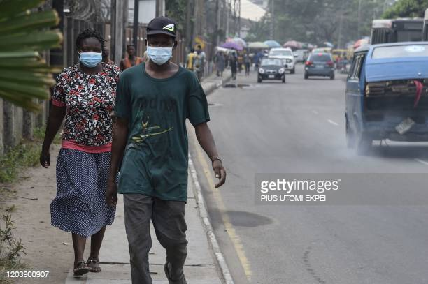 People walk along a main road wearing face masks at Yaba in Lagos, on February 28, 2020. - Residents of Nigeria's economic hub Lagos scrambled for...