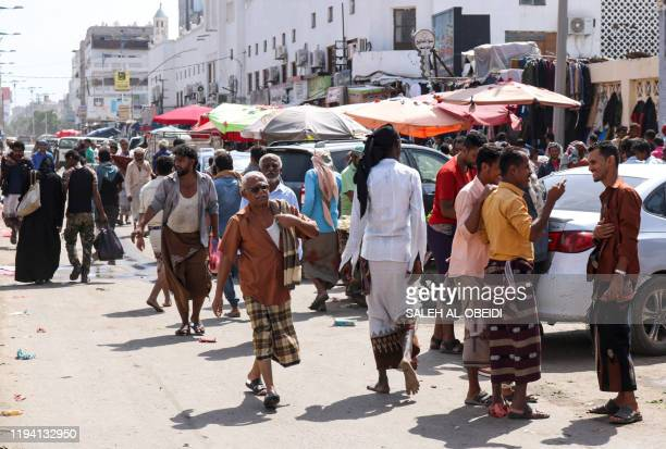 People walk along a market street in the district of Sheikh Othman in Yemen's southern port city of Aden on January 17 2020