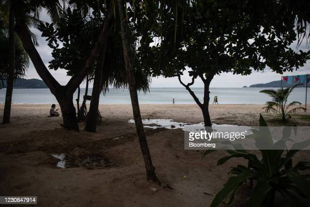 People walk along a near-empty beach in Patong, Phuket, Thailand, on Sunday, Dec. 20, 2020. The tepid response to Thailands highly publicized...