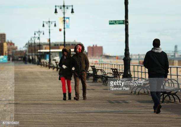 People walk along a nearly empty boardwalk at Coney Island on a chilly afternoon in Brooklyn on November 10 2017 in New York City A cold front is...