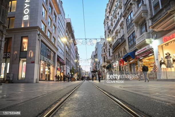 People walk along a nearly empty Istiklal Avenue as the nation tries to contain the novel coronavirus COVID19 in Istanbul on March 172020 Turkey...