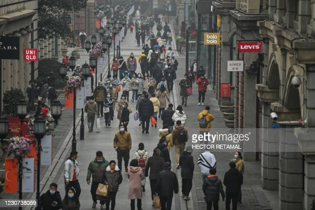 People walk along a pedestrian street in Wuhan, China's central Hubei province on January 23 one year after the city went into lockdown to curb the...