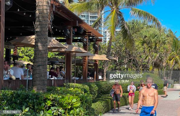 People walk along a restaurant's patio where patrons enjoy lunch in Miami, Florida, on December 20 amid the Coronavirus pandemic.