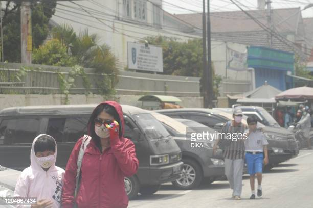 People walk along a road following an eruption by Mount Merapi in Solo on March 3 2020 Indonesia's most active volcano Mount Merapi erupted on March...