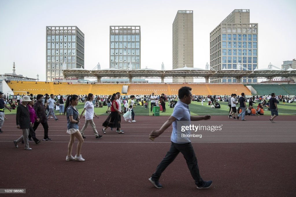 People walk along a running track at a sports stadium in Golmud, Qinghai province, China, on Sunday, July 22, 2018. Amid rising fears about a trade war, China's policy makers have unveiled measures to boost infrastructure construction and credit to smaller firms, as well as tax cuts. Photographer: Qilai Shen/Bloomberg via Getty Images