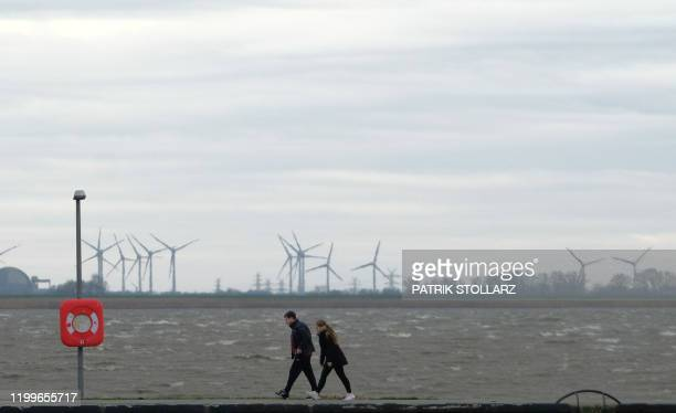 People walk along a seawall at the North Sea in Bremerhaven northern Germany on Febuary 9 2020 The storm named Sabine is estimated arriving along the...