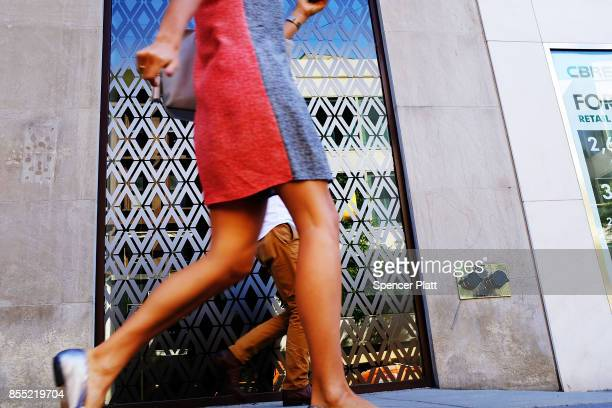 People walk along a sidewalk on Madison Avenue one of the most expensive shopping districts in America on September 28 2017 in New York City The...