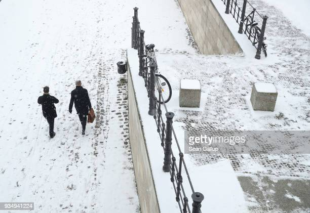 People walk along a snowcovered embankment along the Spree River on March 20 2018 in Berlin Germany Snow is falling across Germany and weather...