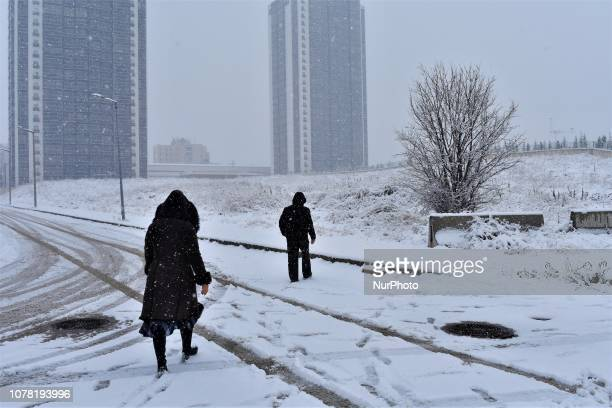 People walk along a snowcovered road during a heavy snowfall in the winter season in Ankara Turkey on January 6 2019