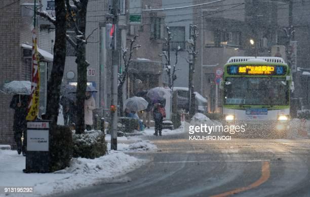 TOPSHOT People walk along a street as it snows in Tokyo on February 2 2018 / AFP PHOTO / Kazuhiro NOGI