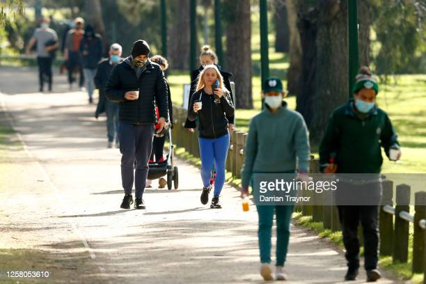 People walk along a street at Princes Park on July 25 2020 in Melbourne Australia Victoria reported seven COVID19 deaths on July 24 the state's...