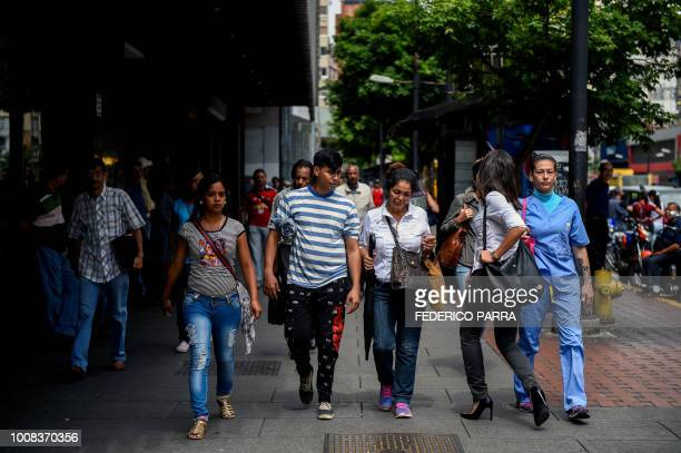 People walk along a street during a partial power cut in Caracas on July 31 2018 A power failure cut electricity to 80 percent of the Venezuelan...