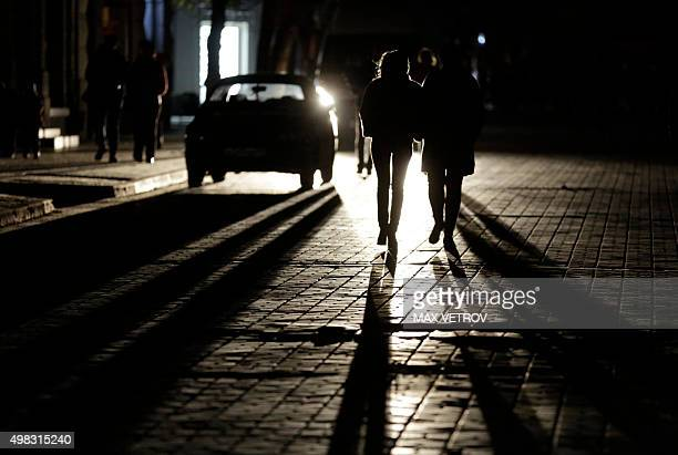People walk along a street in central Simferopol on November 22 2015 Crimea declared a state of emergency on Sunday after its main electricity lines...