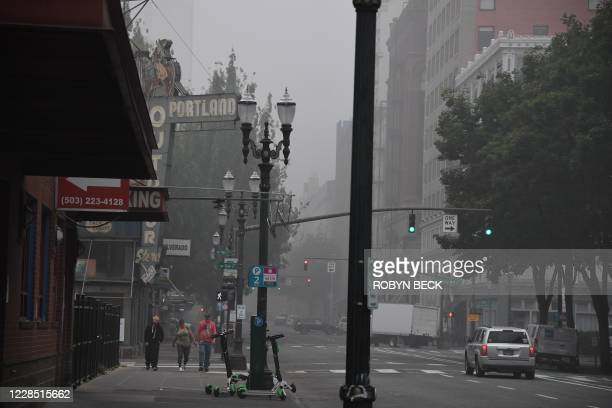 People walk along a street in downtown Portland, Oregon where air quality due to smoke from wildfires was measured to be amongst the worst in the...