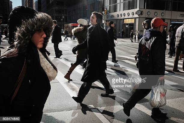 People walk along a street in midtown Manhattan after a recent cold spell on January 5 2016 in New York City Following weeks of some of the warmest...