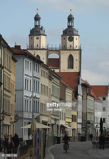 People walk along a street in the historic city center near Stadtkirche Sankt Marien church, where nearly 500 years before theologian Martin Luther...