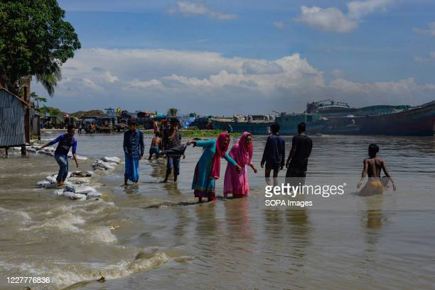 People walk along a submerged road. The flood situation is worsening in Munshiganj. Due to the heavy rain, the water level of the Padma River has...