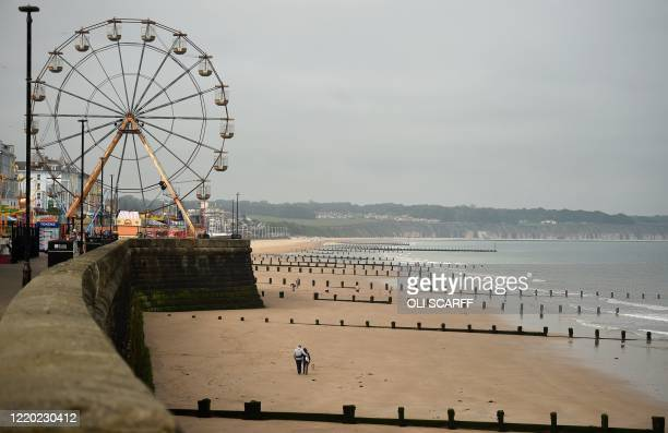 People walk along an empty beach in Bridlington on the north east coast of England on June 15 as some non-essential retailers reopen from their...