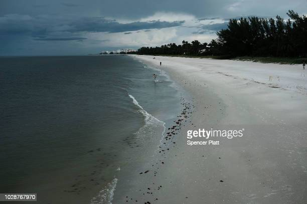 People walk along an empty beach near the Naples Pier on September 7 2018 in Naples Florida Despite being largely clear of the red tide that has...