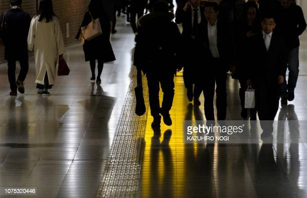 People walk along an underground passage at a railway station in Tokyo on December 28 2018 Tokyo's benchmark Nikkei index closed lower on December 28...