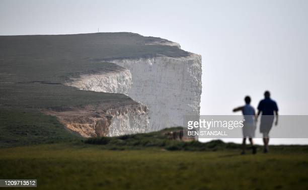 People walk along Beachy Head close to Eastbourne on the south coast of England on April 12 as life in Britain continues over the Easter break during...