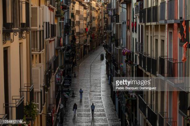 People walk along Calle Estafeta after the San Fermin Festival was cancelled earlier this year, on July 07, 2020 in Pamplona, Spain. The annual...