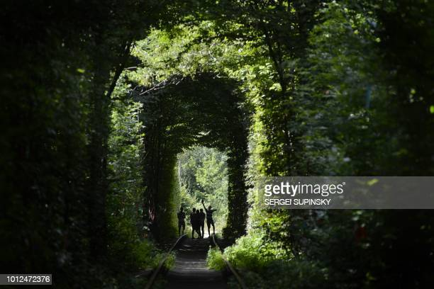 TOPSHOT People walk along former railway tracks surrounded by arches of intertwined trees in the socalled 'Tunnel of Love' near the Ukrainian village...