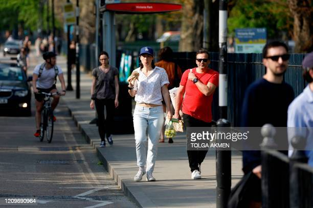 People walk along hte pavement outside Victoria Park, east London on April 11 as life in Britain continues over the Easter break, during the...