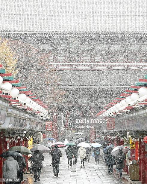 People walk along Nakamisedori an approach to the Sensoji temple one of Tokyo's popular sightseeing spots on the morning of Nov 24 the day when the...