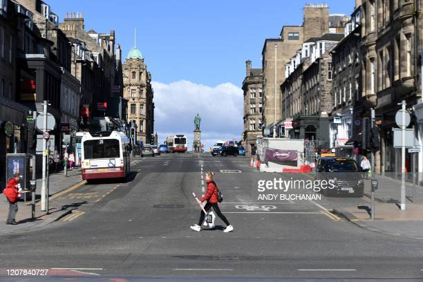 People walk along near deserted streets amidst the novel coronavirus COVID19 outbreak in Edinburgh on March 2020