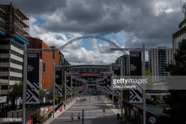 People walk along Olympic Way in front of the stadium shortly before the FA Cup Final kick off at Wembley Stadium on August 1, 2020 in London,...