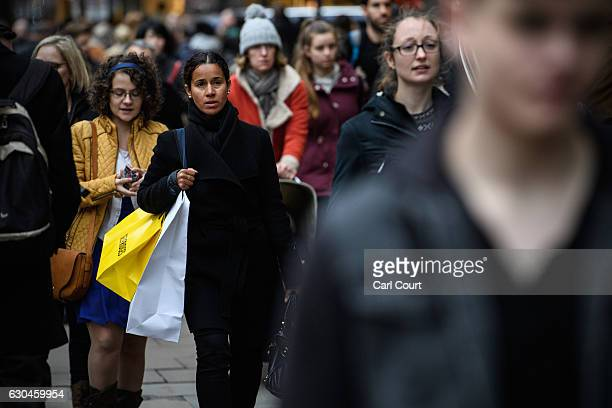 People walk along Oxford Street on December 23 2016 in London England Shoppers are continuing to spend as stores offer bargains in the run up to the...