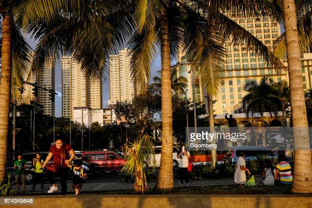 People walk along Roxas Boulevard in Manila Philippines on Sunday Nov 12 2017 Economists are forecasting the Philippines to be among the first to...